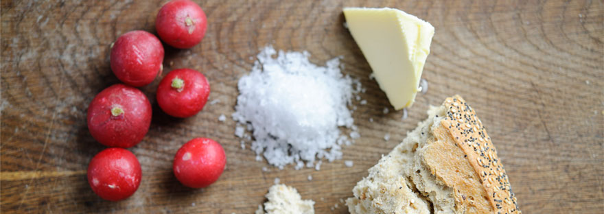 6 red radishes, a small pile of salt, piece of butter and crusty bread on a chopping board